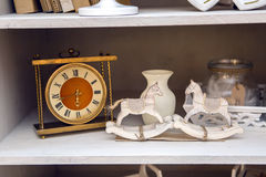 White outdoor small cupboard with trivia books. Clock, wooden horses, jars, candle holders, photo frames Royalty Free Stock Images