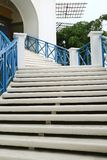 White outdoors staircase with blue railing leads to the upstairs Stock Images