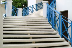 White outdoors staircase with blue railing leads to the upstairs Royalty Free Stock Images