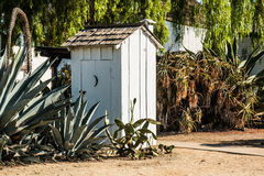 White Outhouse with Cactus Plants in Garden stock images