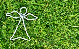 White outline bead angel on freshly cut green grass. White outline of a beaded angel on freshly cut green garden lawn taken from above, close up of grass blades Stock Photo