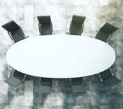 White oval conference table with black leather chairs on concret Royalty Free Stock Photography