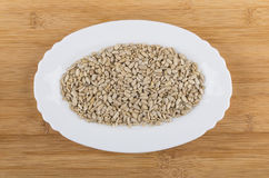 White oval dish with sunflower seeds on wooden table Royalty Free Stock Photo