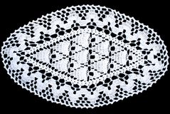 Oval lace tablecloth isolated on black background, close up. White oval lace tablecloth isolated on black background, close up. Cute out and texture for design Stock Photography