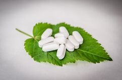 White Oval Medication Pill on Green Leaf Royalty Free Stock Image