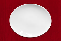 White Oval Plate on Red Fabric Royalty Free Stock Photos