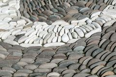 White oval stones stacked arch or semi-circle among the dark stones. The stones are located one behind the other in several rows. Between the stones are small Royalty Free Stock Images
