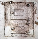 White oven wall, charred mark. Old oven door. Exiting the door hole, filled with brick Royalty Free Stock Image