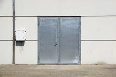 White Overhead Steel Garage Door On Exterior Of Beige Metal Building With Red Bumper Posts.  Stock Photography