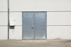 White Overhead Steel Garage Door On Exterior Of Beige Metal Building With Red Bumper Posts.  Royalty Free Stock Photo