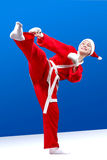 With white overlays on the hands and in a suit santa claus girl beats a kick leg Royalty Free Stock Photography
