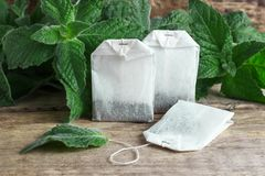 White packages of disposable tea with mint branches on a wooden background Stock Photography