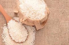 White paddy rice on wooden spoon and the hemp sack. Selective focus with shallow depth of field Royalty Free Stock Photography