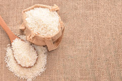 White paddy rice on wooden spoon and the hemp sack. Selective focus with shallow depth of field Stock Image