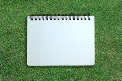 White page of notebook on grass texture Stock Images