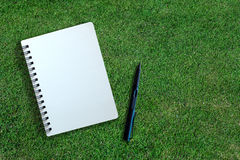 White page of notebook and pen on grass texture Stock Image