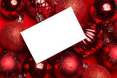 White page on red christmas baubles Royalty Free Stock Photography