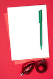 White page with red christmas baubles and pen Stock Photo
