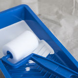 White paint in blue tray with paint roller Stock Photos