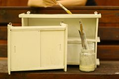 White paint with brushes in jar and old shelfes furniture Stock Image