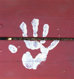 White Paint Hand Print. White painted hand print on red wooden wall royalty free stock image