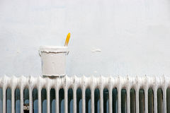 With white paint and paintbrush on radiator. Plastic jar with white paint and paintbrush on radiator Stock Photos