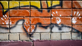 White paint prints of four hands on colourful graffity on a brick wall stock photo