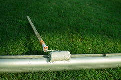 WHITE PAINT ROLLER ON FOOTBALL POST AND GRASS BACKGROUND Stock Images