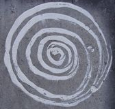 White paint spiral on gray grunge stone wall Stock Photography