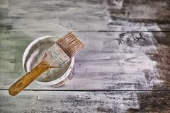 White paint tin and paint brush on the table Royalty Free Stock Photos