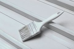 A white paintbrush on a white wooden surface. royalty free stock image