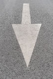 White painted arrow on grey asphalt road Stock Image