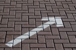 White painted arrow on pavement. Stock Photos