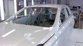 White painted automobiles bodies are moving over conveyor tape