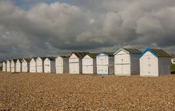 Beach huts at Worthing, Sussex, England. White painted beach huts on the seafront at Goring in Worthing, West Sussex, England Royalty Free Stock Images
