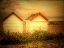 White painted beach huts on West Sussex shingle beach. Two painted wooden beach it's on a shingle beach Royalty Free Stock Image