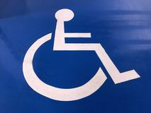 White Painted Handicap Parking Sign. On Blue Floor Royalty Free Stock Image