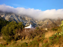 Spanish white painted house, nestled at the foot of the mountain. Stock Photo