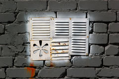 White painted metal vent window in gray brick wall royalty free stock photos