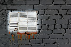 White painted metal vent window in gray brick wall stock images