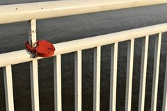 The white painted railing of the embankment of the river. With a red lock in the shape of a heart, mounted on a metal pipe. royalty free stock photo