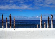 White painted wall with blue sea to the horizon with summer sky. And clouds with old wooden fence posts Royalty Free Stock Photography