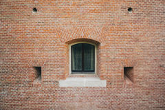 White painted wood arched window in a red brick wall . Stock Image