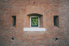 White painted wood arched window in a red brick wall . Royalty Free Stock Image