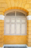 Wood arched window in a yellow wall. White painted wood arched window in a yellow wall Stock Photography