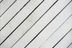 White painted wooden surface close-up. Rustic natural wooden diagonal planks with cracks, scratches for modern design. Patterns, extured background, copy space stock image