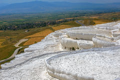 White Pamukkale terraces against rural landscape Stock Images