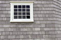 White pane window. A pane window outlined in white against weathered wood shingle building Royalty Free Stock Image