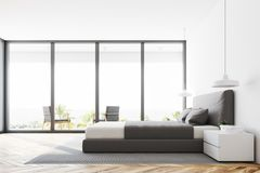 White panoramic bedroom, side view. White panoramic bedroom interior with a wooden floor, a double bed and a magnificent window view. 3d rendering mock up Royalty Free Stock Photo