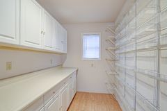 White pantry fitted with shelves and cabinets. White pantry fitted with a wall of floor to ceiling shelves facing white cabinets stock photos